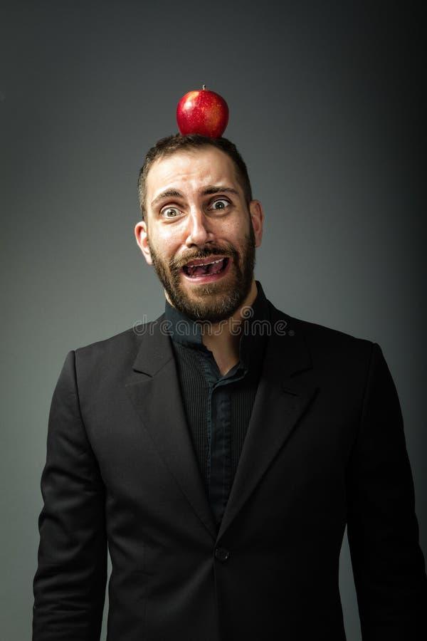 Mensenportret op grijze achtergrond met appel op hoofd royalty-vrije stock afbeelding