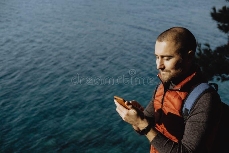 Mensenreiziger in een rode vest het letten op wereldkaart op mobiele pho stock foto's