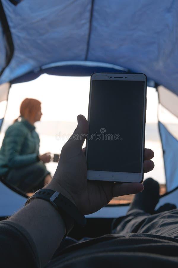 Mensenreiziger in een smartphonegadget van het tentgebruik Binnen mijn tent, enternen het meer en het kamperen, de zomerdag, netw stock afbeeldingen
