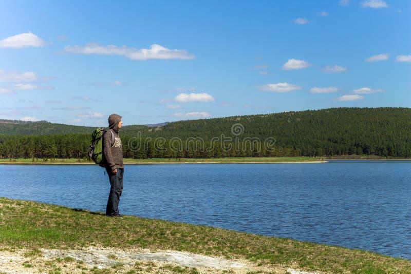 Mensenreiziger met rugzak die zich dichtbij het meer bevinden royalty-vrije stock afbeelding