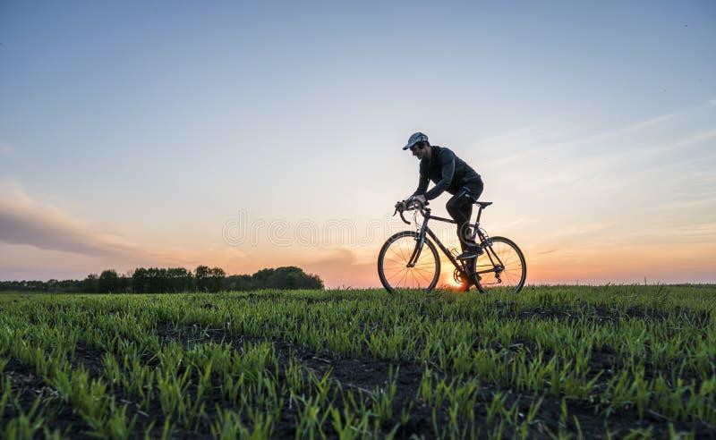 Mensenrit een fiets in zonsondergang Het berijden van een Fiets bij Zonsondergang Gezond levensstijlconcept Mannelijke ritfiets i stock foto