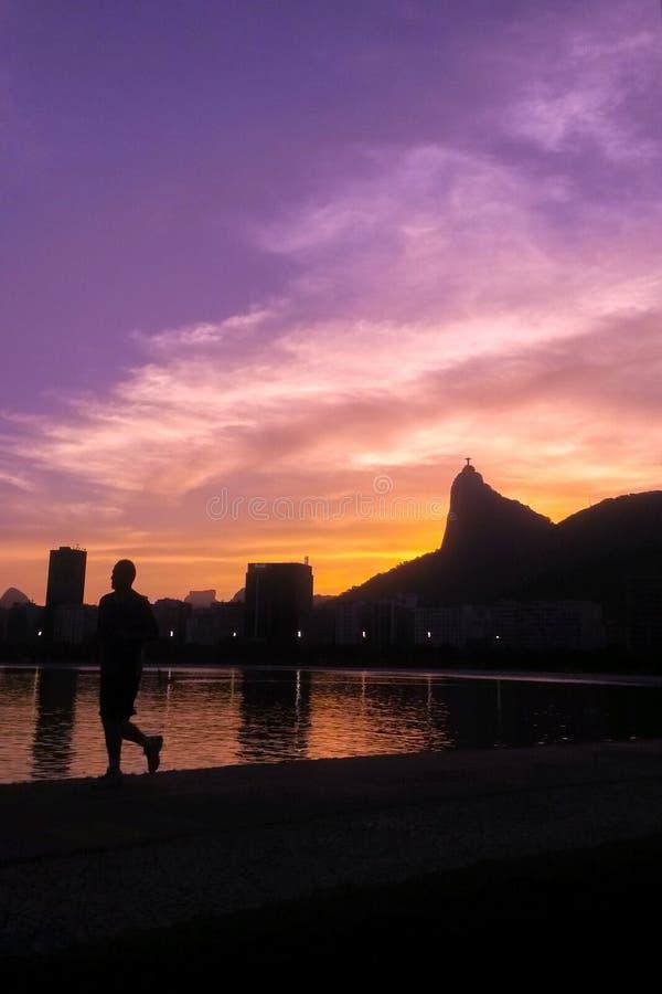 Mensensilhouet die in een overweldigend landschap in Rio de Janeiro tijdens kleurrijke zonsondergang lopen stock afbeeldingen