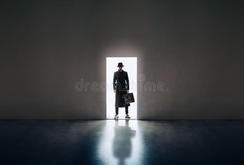 Mensensilhouet die zich in het licht van het openen van deur in donkere roo bevinden stock afbeeldingen