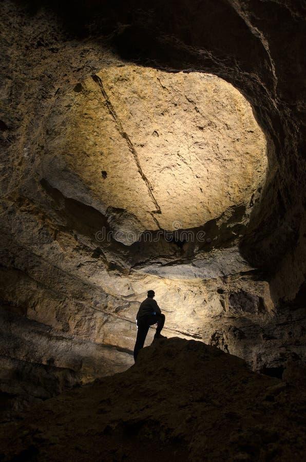Mensensilhouet in een reusachtig donker hol stock afbeelding