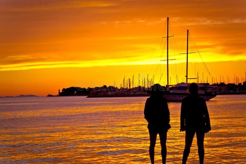 Mensensilhouetten bij gouden zonsondergang op zee stock afbeeldingen