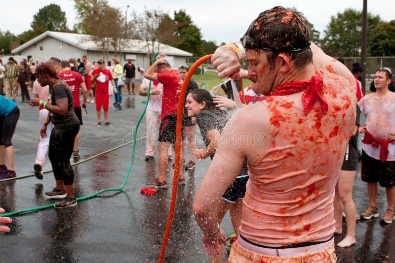 Mensenslangen van Stukken Tomaten na Massieve Voedselstrijd stock foto