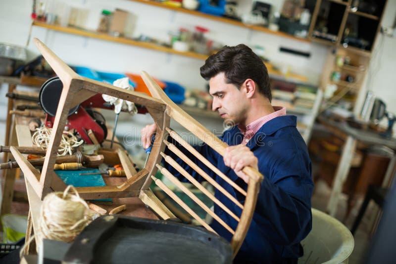 Mensentimmerman in de workshop van de meubilairreparatie stock foto's
