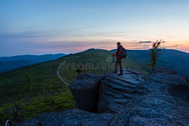 Mensentoerist bij de bovenkant van de rots stock afbeelding