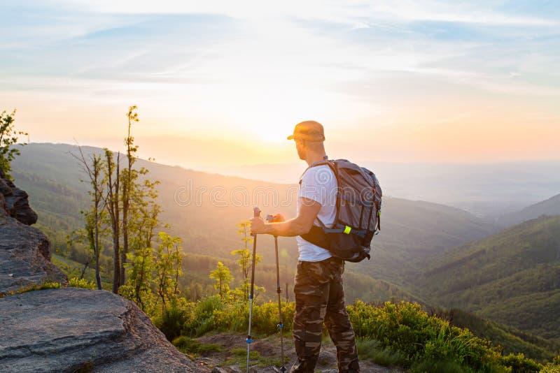 Mensentoerist die met trekkingspolen op mooie zonsopgang letten stock afbeeldingen