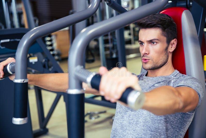 Mensentraining op geschiktheidsmachine in gymnastiek royalty-vrije stock afbeelding