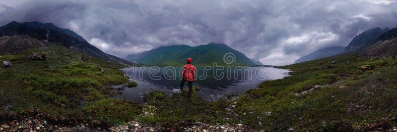 Mensentribunes door meer in rood jasje in bewolkt weer cilindrisch panorama 360vr stock foto's