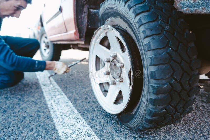 Mensenverandering het wiel manueel op een 4x4 van wegvrachtwagen stock foto's