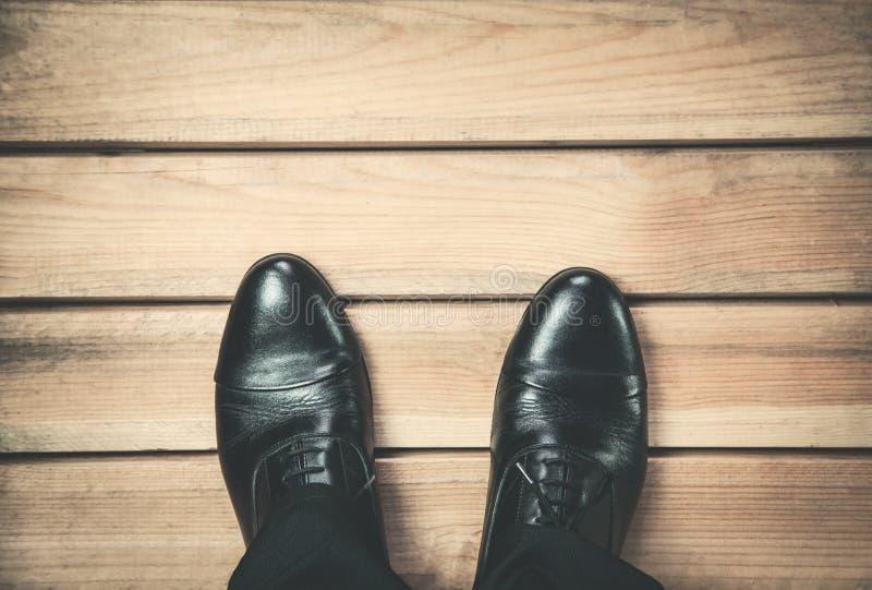 Mensenvoeten in de zwarte tribunes van leerschoenen op houten vloer royalty-vrije stock foto