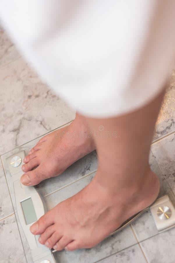 Mensenvoeten die zich op gewichtsschaal bevinden stock afbeelding
