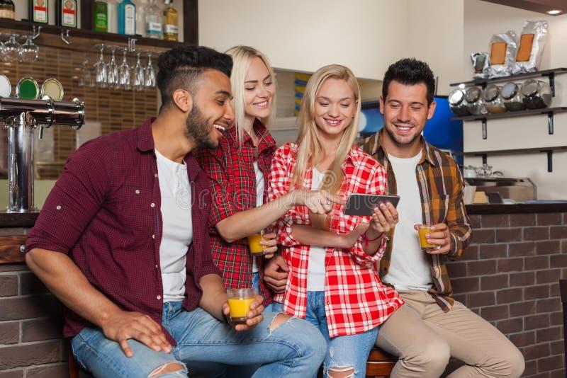 Mensenvrienden die Cel Slimme Telefoon met behulp van, Drinkend Oranje Juice Talking Laughing Sitting At Barteller, de Mens van h royalty-vrije stock afbeeldingen