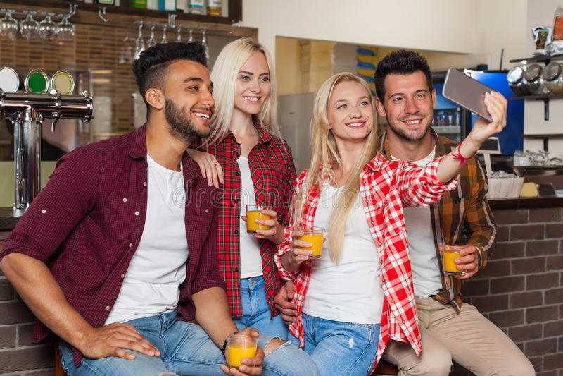 Mensenvrienden die Selfie-Foto het Drinken Jus d'orange nemen, die bij Barteller zitten, de Man van het Mengelingsras de Slimme T stock afbeeldingen