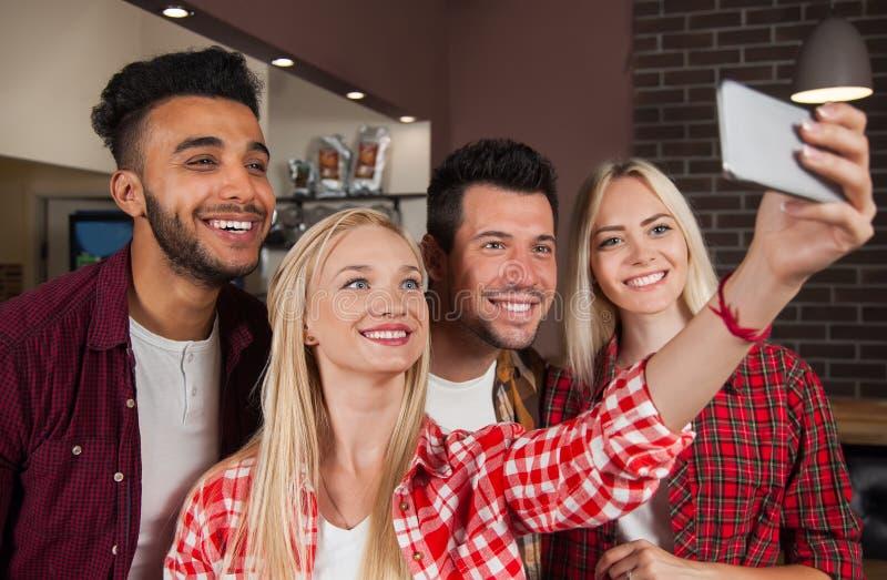 Mensenvrienden die Selfie-Foto nemen bij Barteller, de Man van het Mengelingsras de Slimme Telefoon van de Vrouwengreep stock foto's