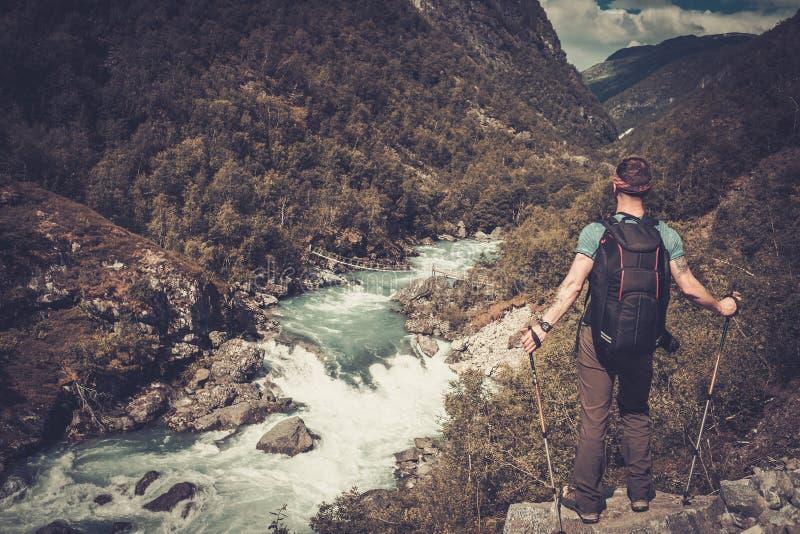 Mensenwandelaar met rugzak die zich op de rand van de klip met de epische wilde mening van de bergrivier bevinden stock fotografie