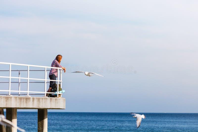 Mensenwandelaar met rugzak op pijler, overzees landschap royalty-vrije stock foto's