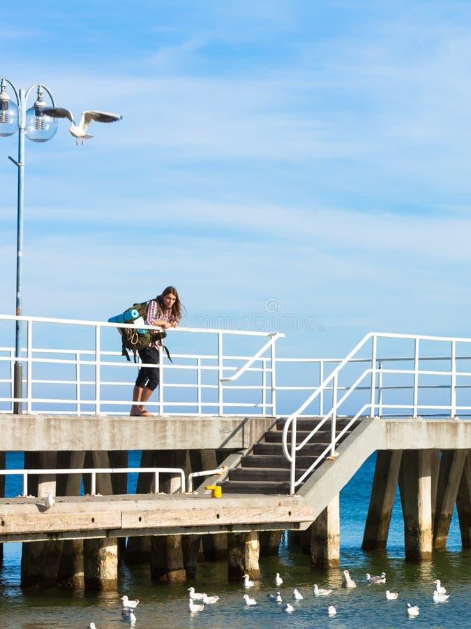 Mensenwandelaar met rugzak op pijler, overzees landschap stock fotografie