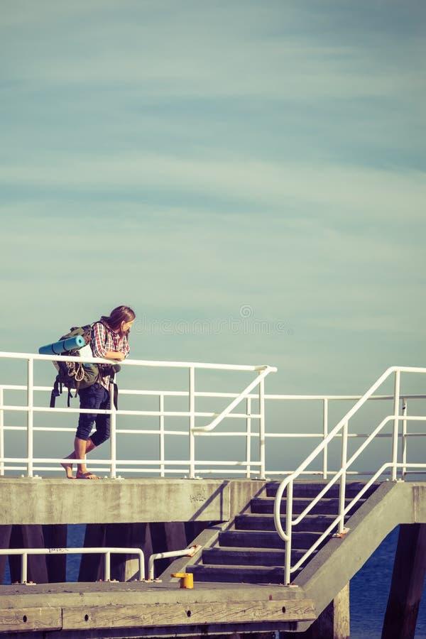 Mensenwandelaar met rugzak op pijler, overzees landschap stock foto