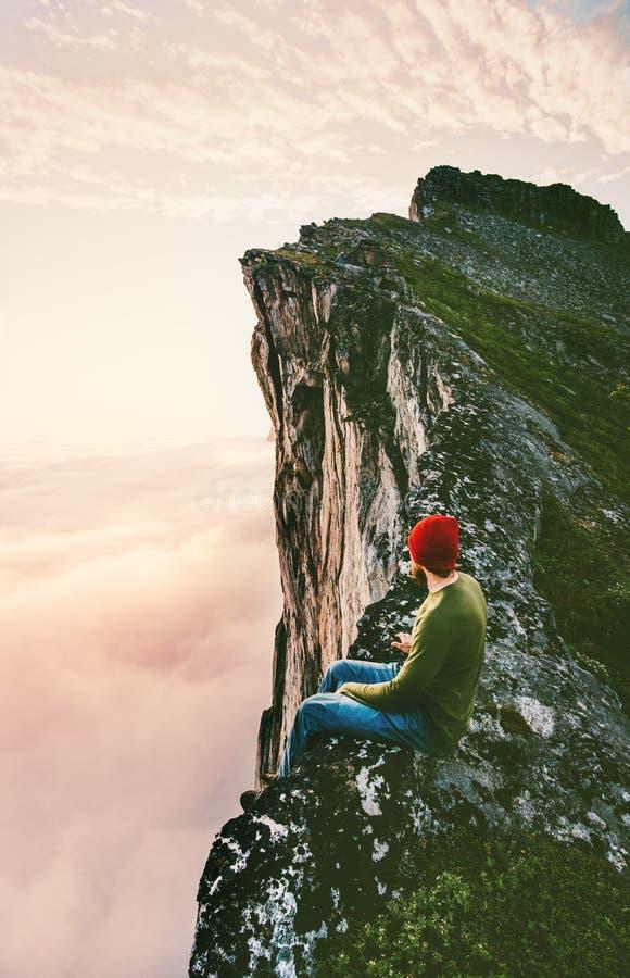 Mensenzitting alleen op de rand van de randberg boven wolken royalty-vrije stock foto's