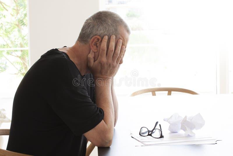 Mensenzitting bij een lijst en het verbergen van zijn hoofd in wanhoop Een paar die glazen op een stapel van documenten met sommi stock foto