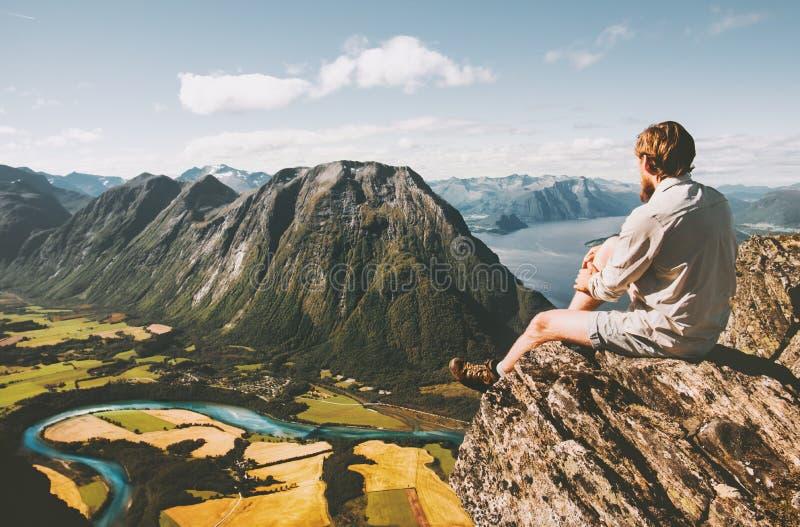 Mensenzitting bij klippenrand het ontspannen met luchtbergenlandschap stock afbeelding