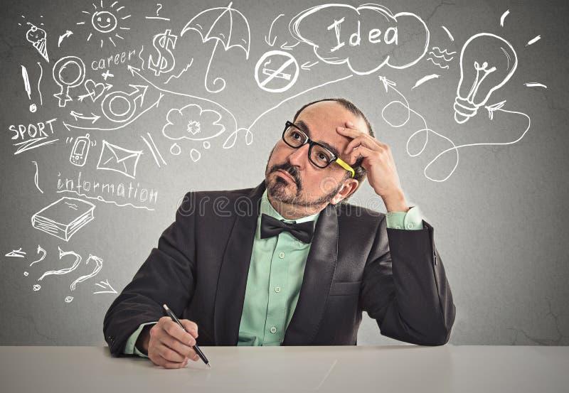 Mensenzitting bij lijst die klaar om iets te schrijven denken stock afbeeldingen