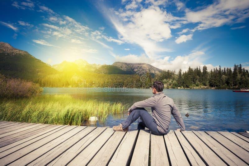Mensenzitting dichtbij alpien bergmeer royalty-vrije stock foto's