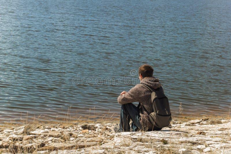 Mensenzitting die alleen en op het meer letten op royalty-vrije stock foto's