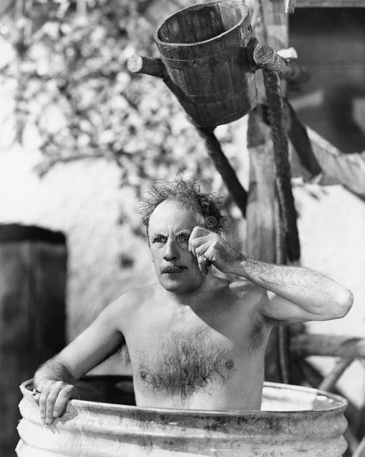 Mensenzitting in een vat die een bad nemen en door zijn monocle kijken (Alle afgeschilderde personen leven niet langer en geen la stock afbeeldingen