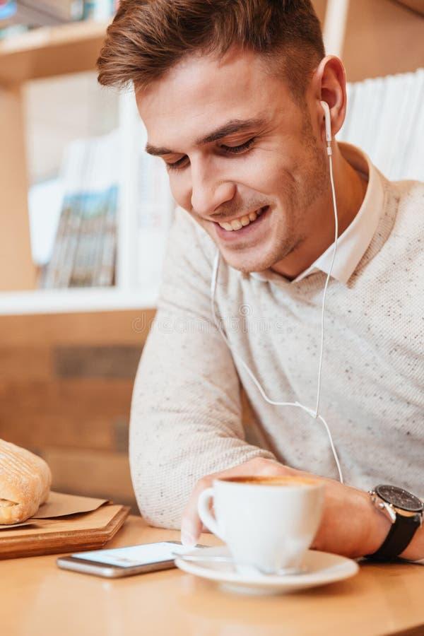 Mensenzitting in koffie terwijl het luisteren muziek en het drinken koffie stock fotografie