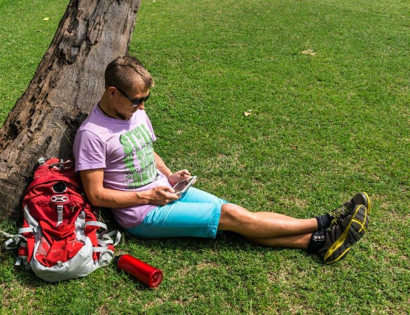 Mensenzitting onder de boom en het gebruiken van zijn tablet royalty-vrije stock foto's