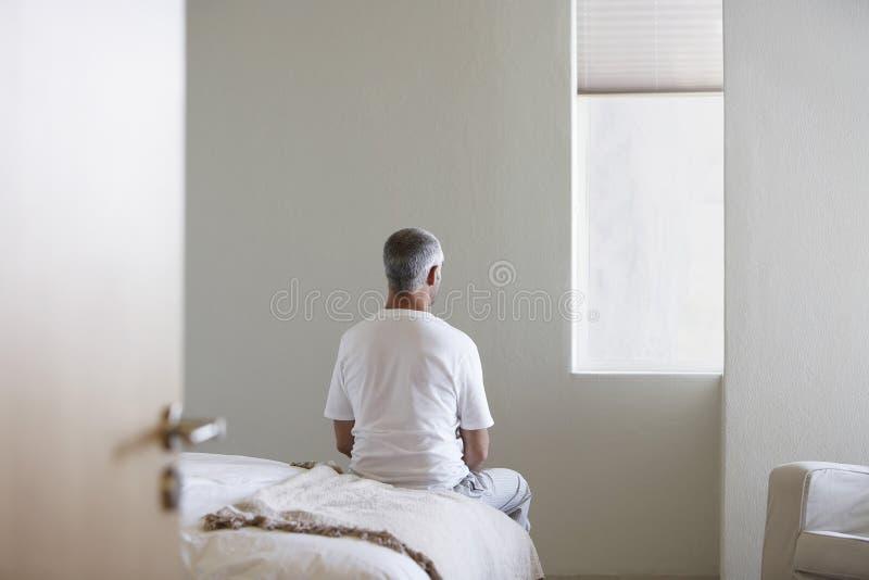Mensenzitting op Bed in Slaapkamer royalty-vrije stock foto