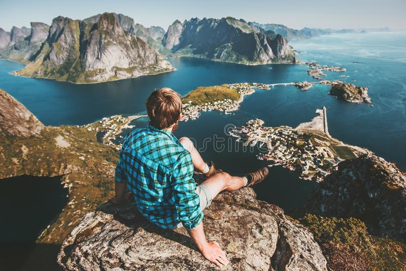Mensenzitting op berg hoogste klip boven overzees en rotsen stock foto