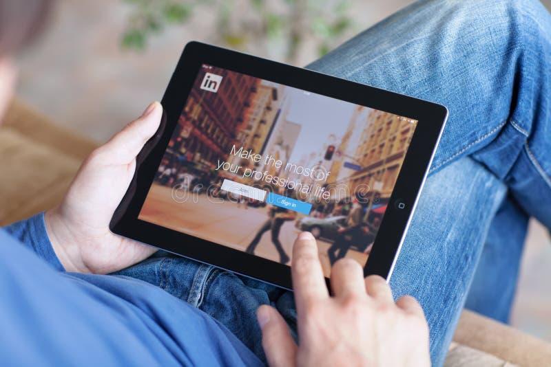 Mensenzitting op de bank en holding iPad met App LinkedIn op Th royalty-vrije stock fotografie