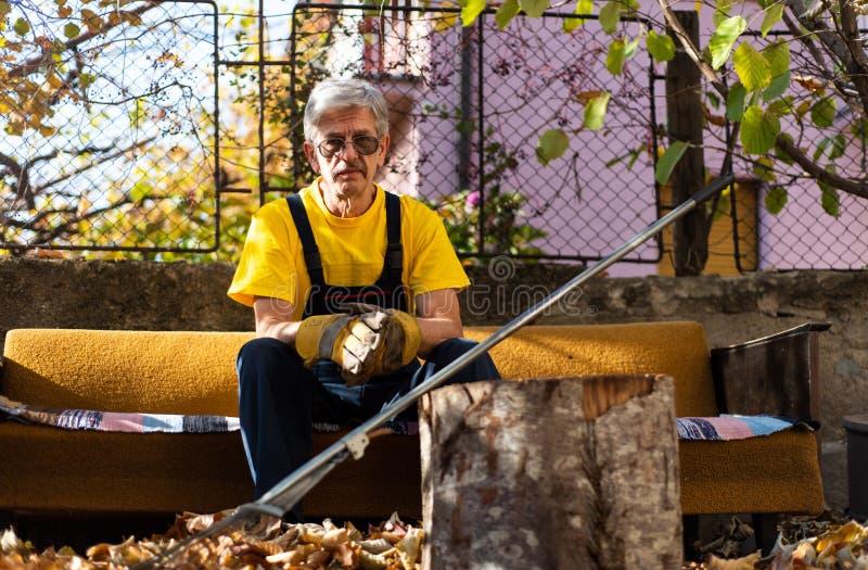 Mensenzitting op de bank na het schoonmaken in de yard stock fotografie