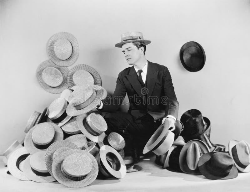 Mensenzitting op de vloer door hoeden wordt omringd (Alle afgeschilderde personen leven niet langer en geen landgoed dat bestaat  royalty-vrije stock foto's