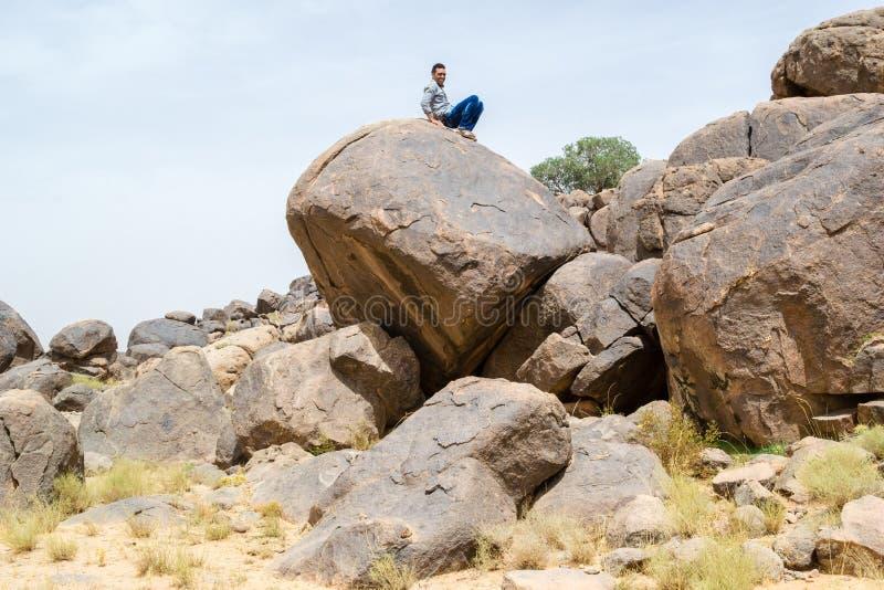 Mensenzitting op een grote rots in de woestijn stock foto's