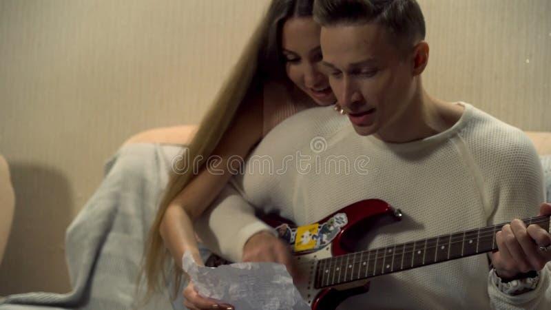Mensenzitting op een laag, het spelen gitaar met een omhelzing van zijn meisje De jonge mens speelt de elektrische jonge gitaar, stock afbeelding