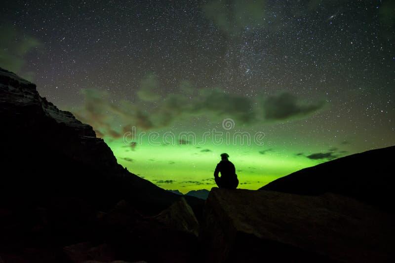 Mensenzitting op een rots in de bergen die op de Noordelijke Lichten letten stock afbeeldingen