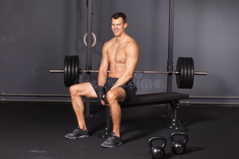 Mensenzitting op een trainingplaats en het glimlachen aan camera stock afbeelding