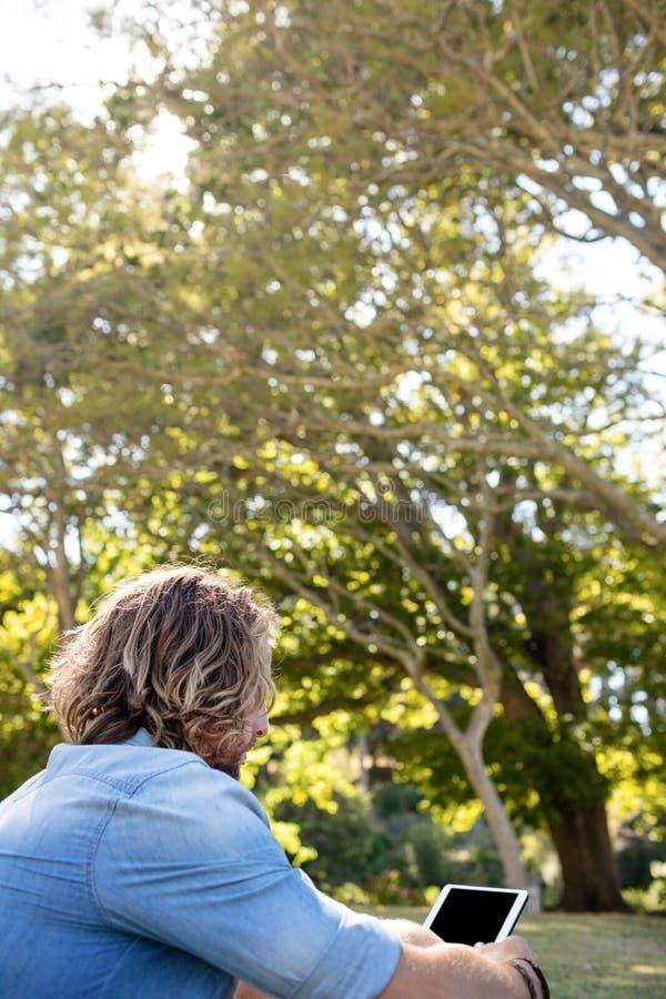 Mensenzitting op gras die digitale tablet gebruiken stock afbeelding