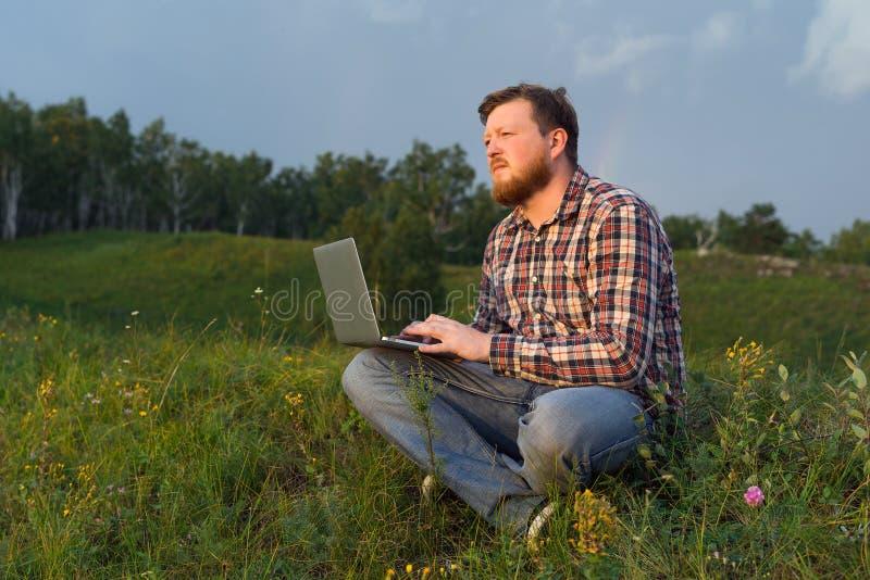 Mensenzitting op het gras met laptop stock afbeelding