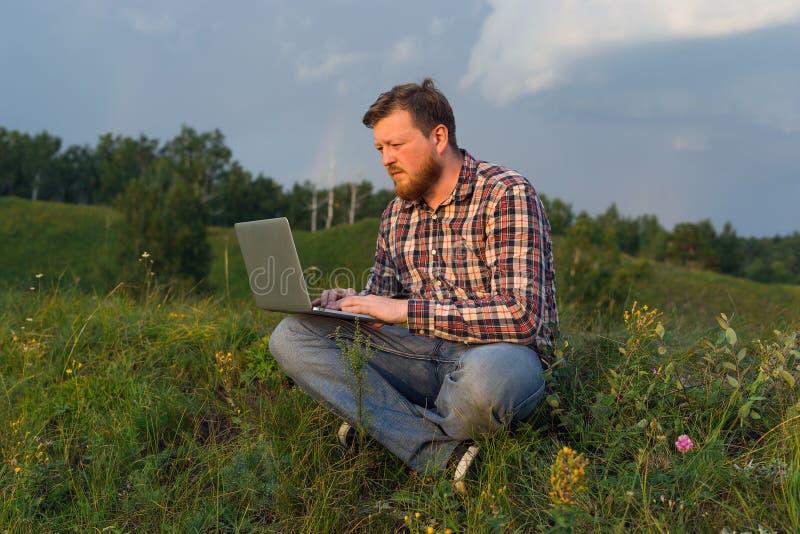Mensenzitting op het gras met laptop op zijn knieën stock afbeeldingen