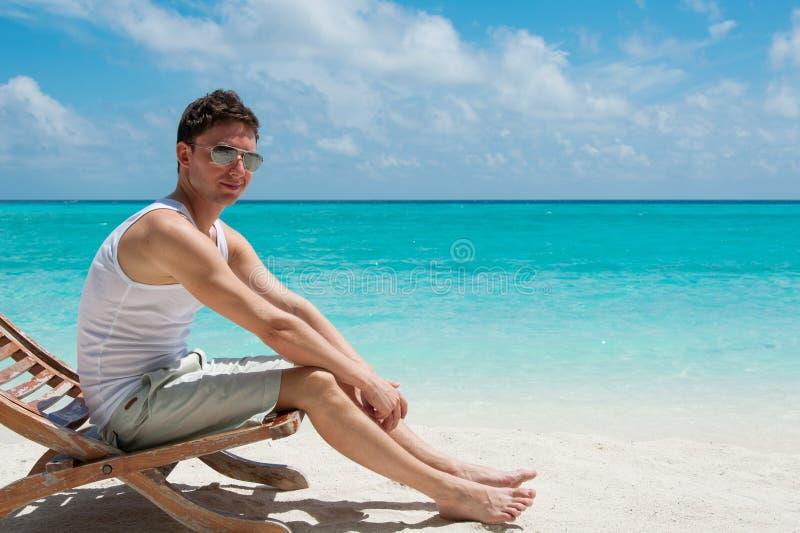 Mensenzitting op het strand die van de zon genieten royalty-vrije stock foto