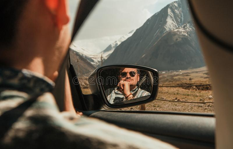 Mensenzonnebril die bergenautoraam weerspiegelde spiegel kijken stock afbeelding