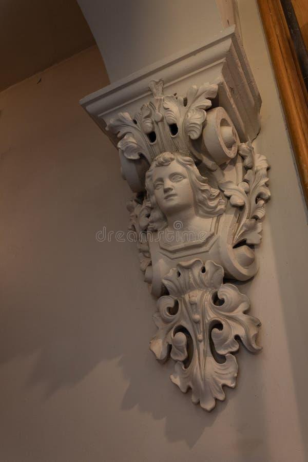 Mensolone decorativo in una casa con il busto di una donna, gesso fuso dipinto fotografie stock