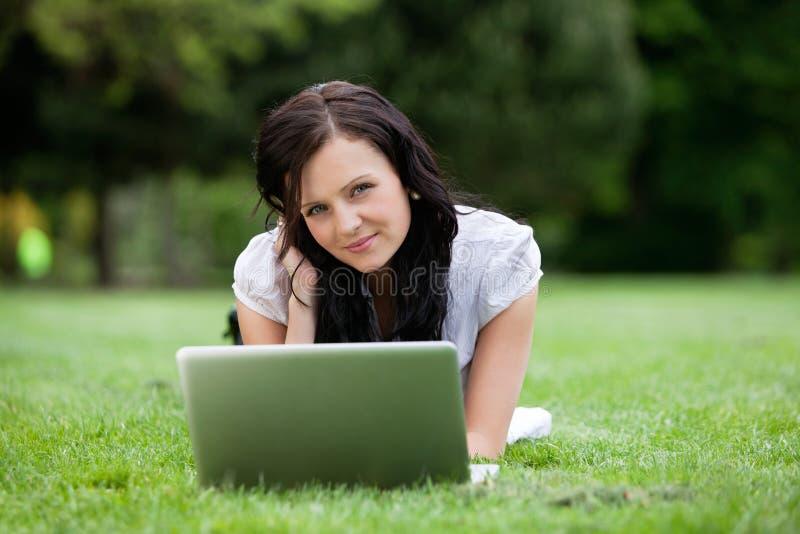 Mensonge assez femelle sur l'herbe avec l'ordinateur portable image stock